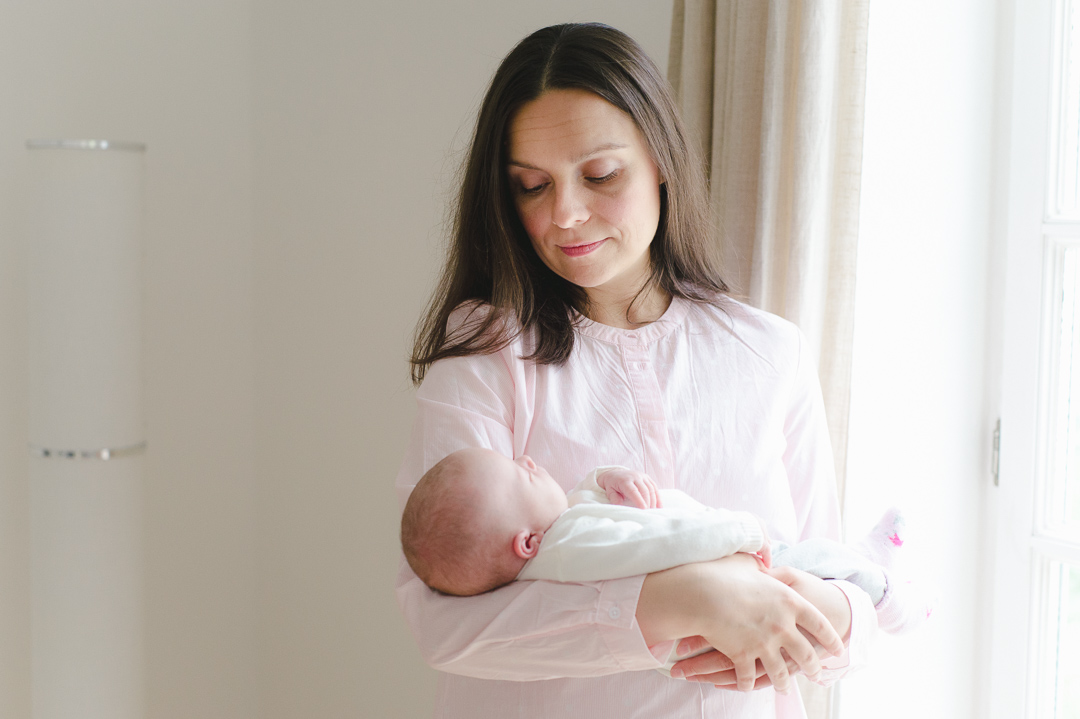Neue Mama hält Baby im Arm