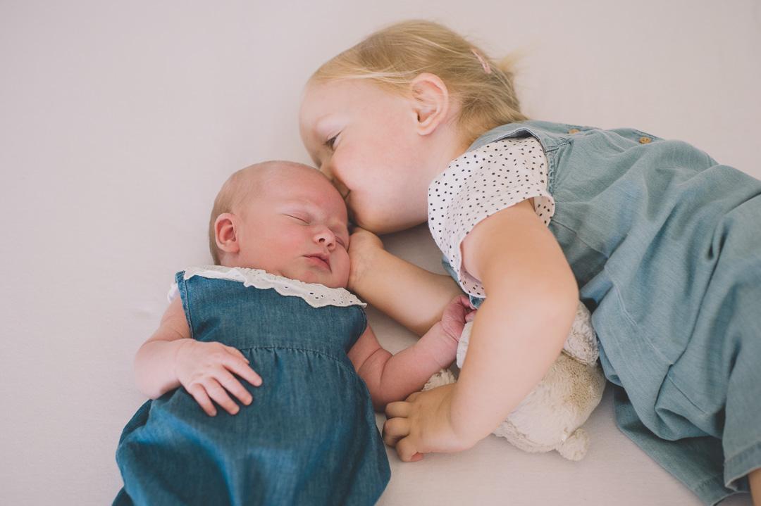 Große Schwester küsst Baby Schwester